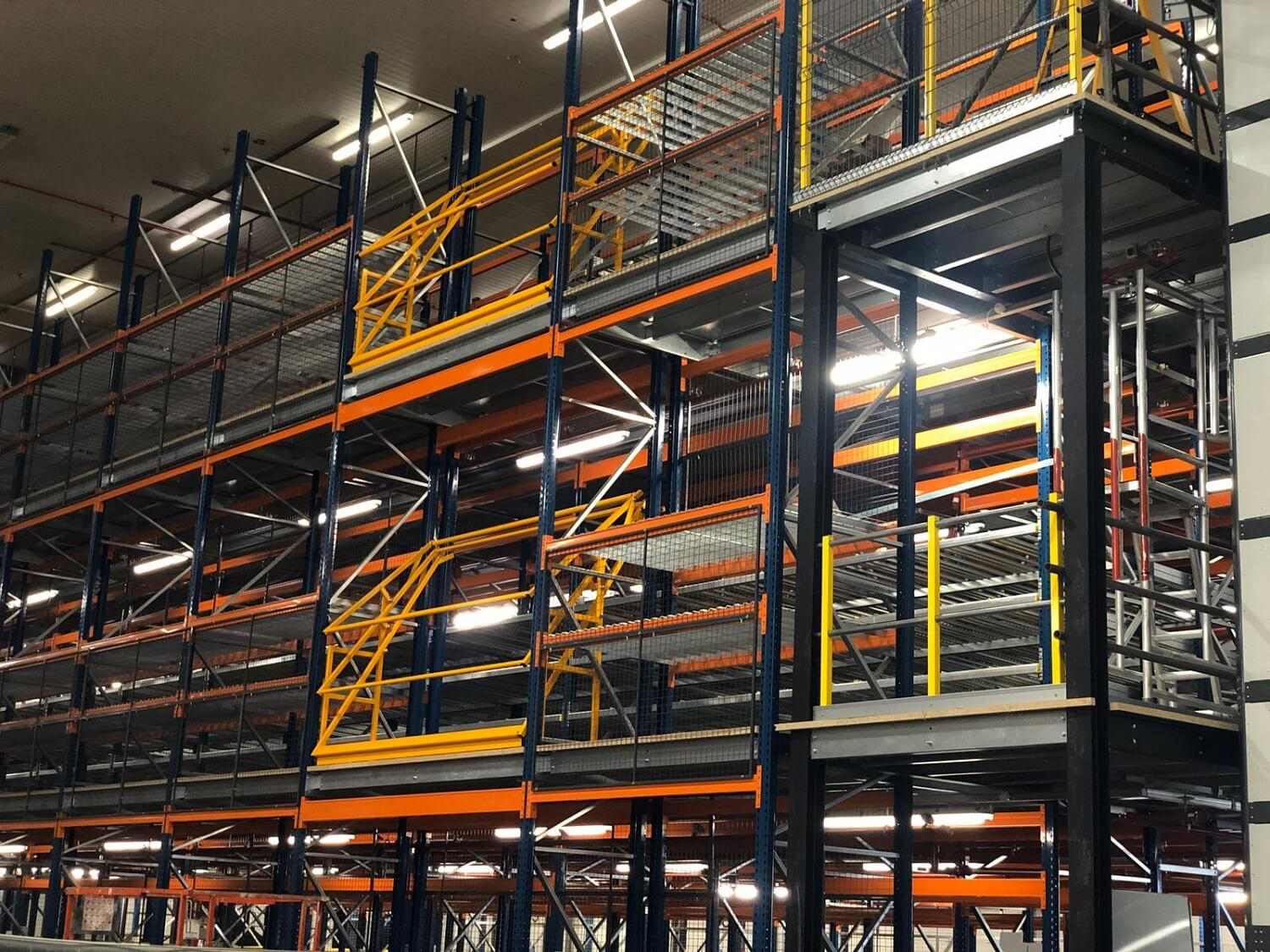 Multi tier pallet racking system with mezzanine floor and pallet gates