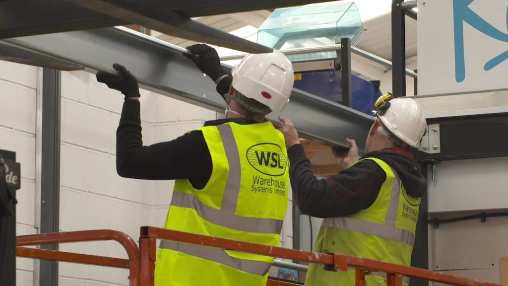 two installer lifting a beam into position