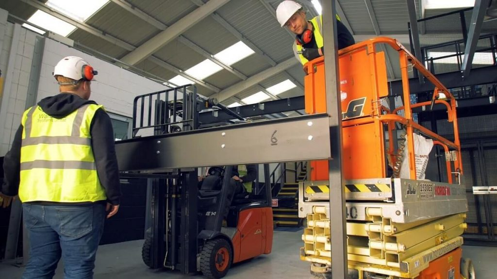 two installers lifting beam into position using scissor lift